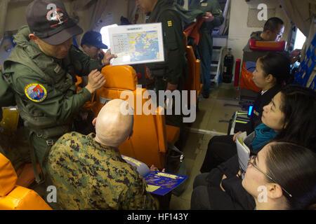 A Japanese Maritime Self Defense Force (JMSDF) service member, left, explains to Public Affairs Marines Maj. Neil - Stock Photo