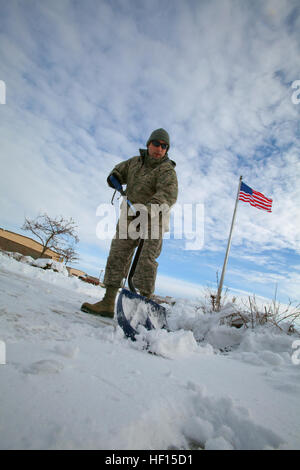 Senior Master Sgt. Matt Johnson removes snow from the 108th Wing's headquarters' walkway at Joint Base McGuire-Dix - Stock Photo