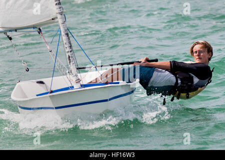 Nolan Laramore, 15, from Honolulu, counterbalances the force of the wind on the sail by hiking his body out over - Stock Photo