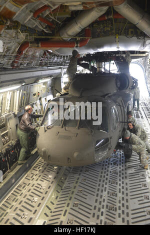 Airmen and soldiers from the Nebraska National Guard push two UH-60 Black Hawk helicopters onto a C-17 from the - Stock Photo