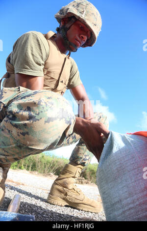 Lance Cpl. Kevin C. Greaves attaches sand bags to a VS-17 platform on Tinian's Backer Runway at North Field Nov. - Stock Photo