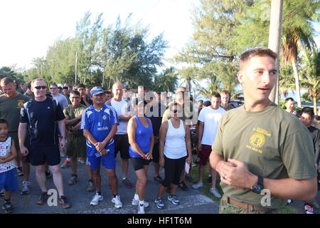 1st Lt. Alex Cloninger explains the course for the 2nd Tinian Hafa Adai 5K run to participants waiting at the starting - Stock Photo