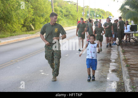 1st Lt. Alex Cloninger runs alongside Harry Fang, 8, who finished the run with a time of 24 minutes 14 seconds during - Stock Photo