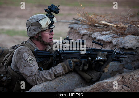 Lance Cpl. Nathan Chandler, a Logan, Ohio, native and machine gunner with 1st Battalion, 9th Marines, hunkers down - Stock Photo