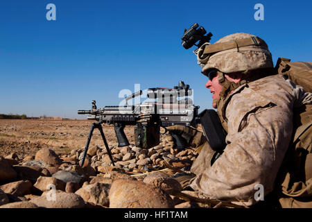 Lance Cpl. Nathan Chandler, a Logan, Ohio, native and machine gunner with 1st Battalion, 9th Marines, lies behind - Stock Photo
