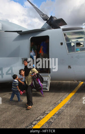 Community members exit an MV-22B Osprey static display Dec. 4 at Rimba Air Base, Brunei, during the 4th biennial - Stock Photo