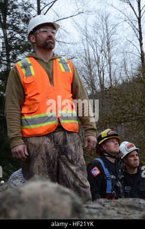 Rescue workers at the Oso mudslide watch as a U.S. Soldier with the Washington Army National Guard rappels from - Stock Photo