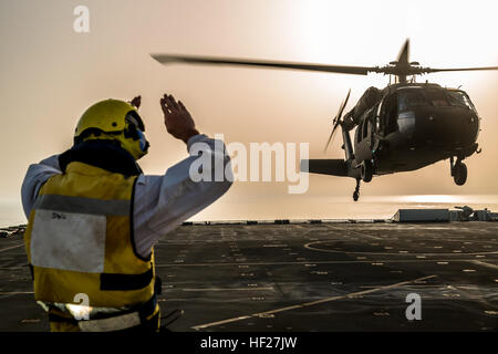 A deck hand on the RFA Cardigan Bay, Royal Fleet Auxiliary, U.K. Royal Navy, gives the signal to lift off to a UH - Stock Photo