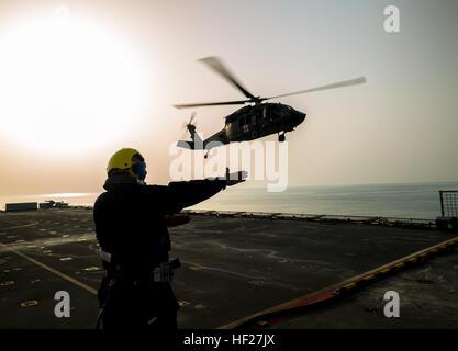 Petty Officer Ian Walker, a deck hand on the RFA Cardigan Bay, Royal Fleet Auxiliary, U.K. Royal Navy, gives the - Stock Photo