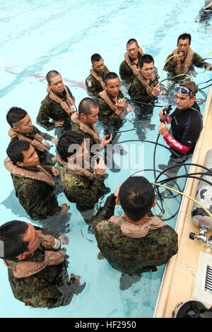 Japan Ground Self-Defense Force soldiers receive instruction during shallow water egress training (SWET) at Camp - Stock Photo