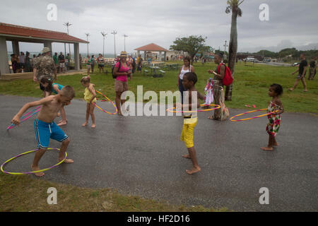 Children hula hoop Aug. 8 during a beach bash at the United States Army Garrison Torii Station beach. The beach - Stock Photo