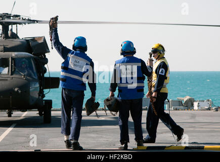 Members of the British Royal Navy demonstrate that they have detached chains and blocks used to tie the UH-60 Blackhawk, - Stock Photo