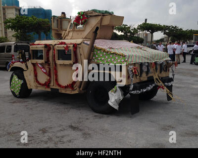 A Humvee is decorated as a float with Christmas ornaments and stockings during the 2014 Camp Kinser Tree Lighting - Stock Photo