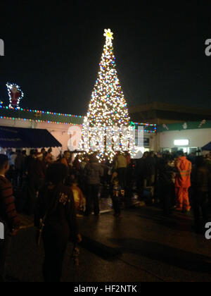 Marines, Okinawa community members and their families huddle around a Christmas tree when it was lit during the - Stock Photo