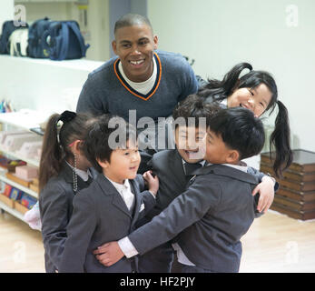 Petty Officer 1st Class De'Angelo Wynn plays a game with students from St. Paul's Elementary School in Pohang, South - Stock Photo