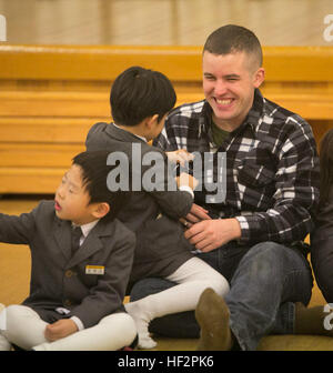 Petty Officer 3rd Class Joshua Gregg interacts with a student of St. Paul's Elementary School in Pohang, South Korea. - Stock Photo