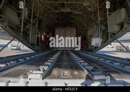 A sea shipping container is loaded onto a KC-130J Super Hercules during a Flight In Support of a Deployed Unit (FISDU) - Stock Photo