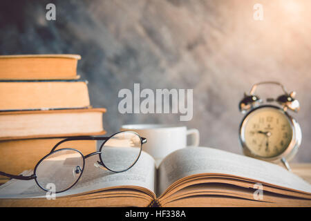 Reading glasses on old book with alarm clock - Stock Photo