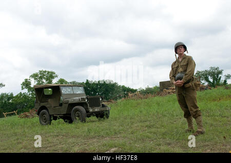 An American World War II reenactor stands and waits to reenact a battle against German reenactors for a crowd of - Stock Photo