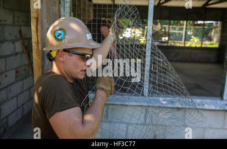 KIRABATI (June 3, 2015) – Steelworker 3rd Class Jonathon Walsh removes wire as part of a construction project to - Stock Photo
