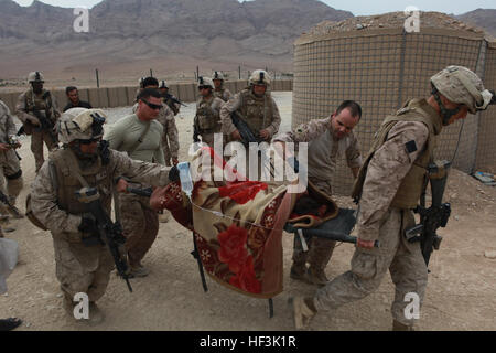 U.S. Marines and Sailors with India Company, 3rd Battalion, 4th Marine Regiment transport an injured Afghan boy - Stock Photo