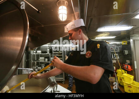 GULF OF ADEN (Oct. 29, 2015) U.S. Marine Cpl. Zachary Zottoli cleans a steam kettle during the preparation for the - Stock Photo