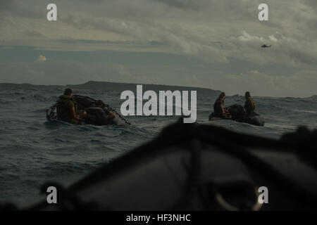 Marines with the Maritime Raid Force, 31st Marine Expeditionary Unit, watch as a UH-1Y Huey flies by during helocast - Stock Photo