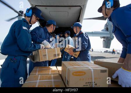 Japan Maritime Self Defense Force personnel, U.S. Navy sailors and U.S. Marines load supplies onto a U.S. Marine - Stock Photo