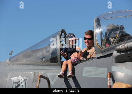 A U.S. Marine poses with a child in the cockpit of an AV-8B Harrier during the 2016 Marine Corps Air Station (MCAS) - Stock Photo