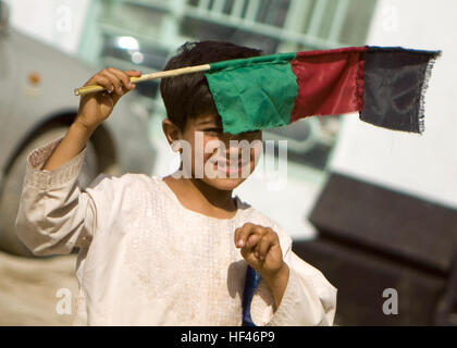 A young Afghan boy uses a homemade Afghan flag to shield his eyes from the sun March 21, during a celebration of - Stock Photo