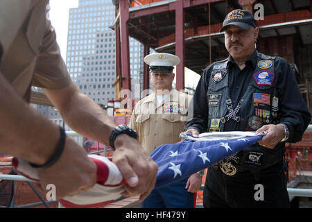 Marine Master Sgt. William Gibson, Jr, helps fold an American Flag, after it flew over the World Trade Center construction - Stock Photo