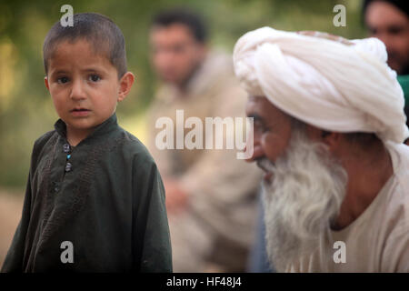 A local Afghan boy looks on as his father talks to U.S. Marines assigned to Bravo Company, 1st Reconnaissance Battalion, - Stock Photo