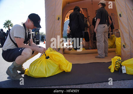 A member of the 91st Civil Support Team from the Arizona National Guard tags a Tempe police officer's bag of belongings - Stock Photo