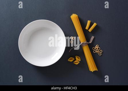 Italian pasta and empty plate - Stock Photo