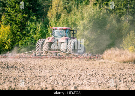 Tractor plowing using a  chisel plow - Stock Photo