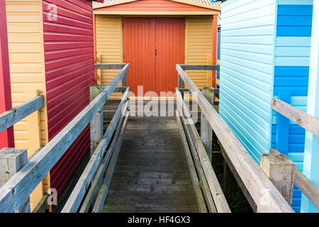 England, Whitstable. Beach huts on seafront, wooden walkway with railing between two huts to hut behind in second - Stock Photo
