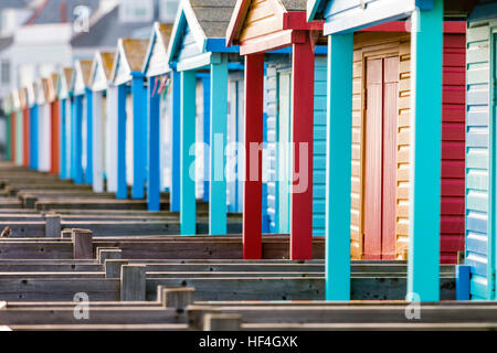 England, Whitstable. Beach huts on seafront, various colours. Row of wooden supports for over hanging doorway roof. - Stock Photo