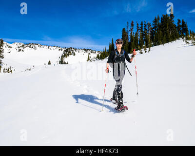 A young woman snowshoeing in the mountains of Mount (Mt) Rainier National Park - Stock Photo