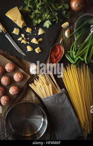 Ingredients for cooking spaghetti, meatballs with cheese and fresh herbs vertical top view - Stock Photo