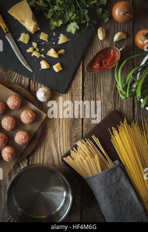 Ingredients for cooking spaghetti, meatballs with cheese and fresh herbs vertical copy space - Stock Photo