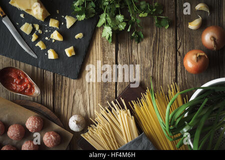 Ingredients for cooking spaghetti, meatballs with cheese and fresh herbs horizontal copy space