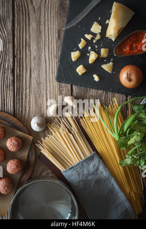Ingredients for cooking spaghetti, meatballs with cheese and fresh herbs on the old table vertical - Stock Photo