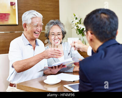 happy senior asian couple ready to sign contract taking a pen from a sales rep. - Stock Photo