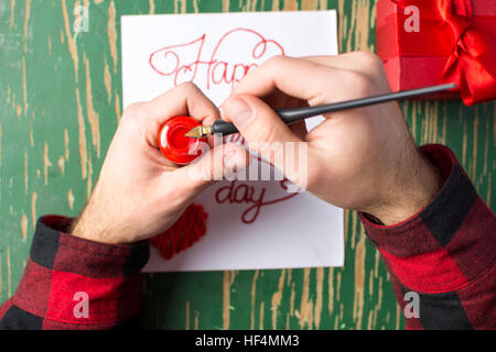 Male hands writing a calligraphy Valentines day card - Stock Photo