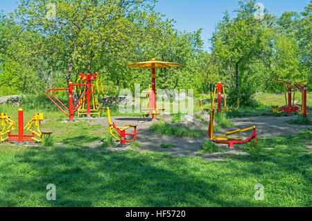 Fitness equipment in a public park on a sunny spring morning - Stock Photo