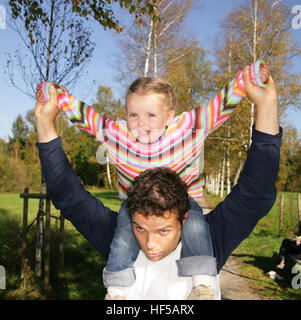 Father giving his three-year-old daughter a piggyback ride - Stock Photo