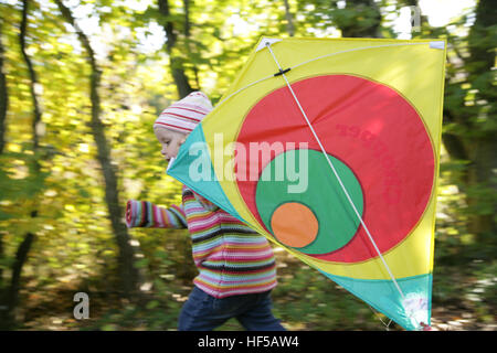 Three-year-old girl playing with kite - Stock Photo