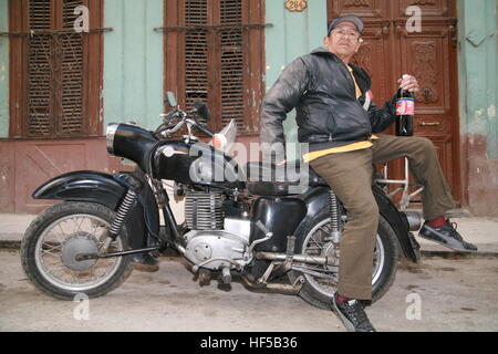 An elderly man sitting on his vintage motorcycle holding a bottle of Cuban cola (tu cola), Havana, Cuba, Caribbean, - Stock Photo