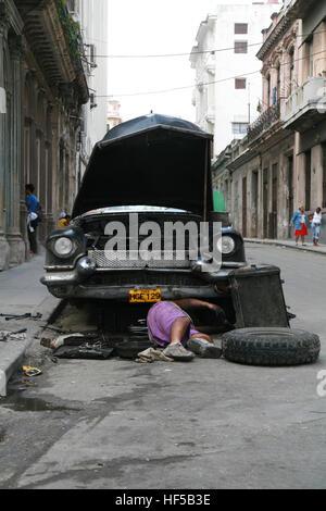 Mechanic fixing a car on a street in Havana, Cuba, Caribbean, Americas - Stock Photo
