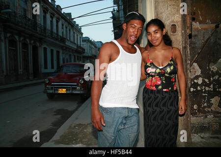 Young couple and vintage car in the background, Havana, Cuba, Caribbean, Americas - Stock Photo